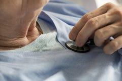 Primer de la mujer mayor que comprueba golpes de corazón con el estetoscopio imágenes de archivo libres de regalías