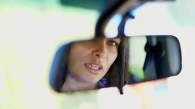Primer de la mujer morena hermosa, artista, sentándose en el coche, mirando en el espejo de la vista posterior ella la endereza almacen de metraje de vídeo