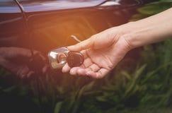 Primer de la mujer que abre una puerta de coche Mano en la manija Foto de archivo libre de regalías