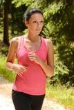 Primer de la mujer que activa que corre en campo Fotografía de archivo libre de regalías