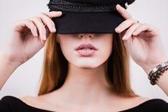 Primer de la mujer que la cubre ojos con el casquillo de moda negro Moda, moda, cosméticos, labios atractivos Fotografía de archivo