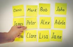 Primer de la mujer que elige el nombre del bebé escrito en etiquetas engomadas Imagenes de archivo