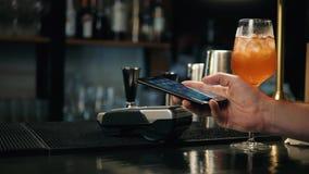 Primer de la mujer que hace el pago con NFC en la panadería, barra del restaurante del café para la limonada del cóctel, teléfono metrajes