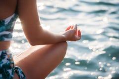 Primer de la mujer que hace yoga en la playa Forma de vida sana imagen de archivo