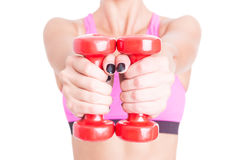 Primer de la mujer que lleva a cabo pares de pesas de gimnasia rojas Foto de archivo libre de regalías