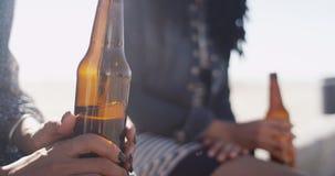Primer de la mujer que sostiene la botella de cerveza con el amigo en fondo imágenes de archivo libres de regalías