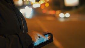 Primer de la mujer que usa la PC de la tableta al aire libre en la ciudad en la noche, solamente manos que se verán metrajes