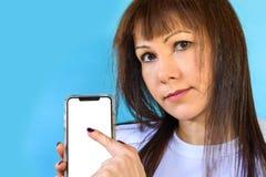 Primer de la mujer que usa smartphone Mofa encima de la pantalla en blanco del color blanco del teléfono móvil fotografía de archivo