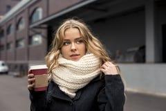 Primer de la mujer rubia caucásica joven hermosa que sostiene el café para llevar al aire libre en parque en otoño Fotografía de archivo libre de regalías
