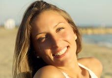 Primer de la mujer rubia joven hermosa con los ojos azules que sonríe en la playa Fotos de archivo libres de regalías
