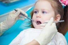 Primer de la niña bonita que abre el suyo boca de par en par durante la inspección de la cavidad bucal en el dentista Foto de archivo libre de regalías
