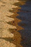 Primer de la orilla con agua en una playa arenosa que forma curvas y formas imágenes de archivo libres de regalías