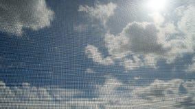 Primer de la pantalla de alambre del mosquito con el rayo del sol en el cielo azul y las nubes blancas en fondo Fotos de archivo libres de regalías