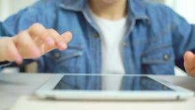 Primer de la pantalla táctil de los fingeres del niño de la tableta mientras que juega a juegos en línea almacen de metraje de vídeo
