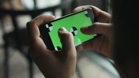 Primer de la pantalla verde conmovedora de las manos masculinas en el teléfono móvil El individuo enfoca adentro y enfoca hacia f metrajes