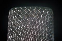 Primer de la parrilla del micrófono del alambre de acero en un fondo negro Tiroteo macro con la profundidad del campo baja r fotos de archivo