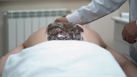 Primer de la parte posterior del hombre durante el tratamiento del abrigo del cuerpo del chocolate Resto en balneario almacen de metraje de vídeo