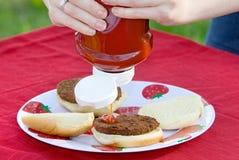 Primer de la persona que pone la salsa de tomate en la hamburguesa Foto de archivo libre de regalías