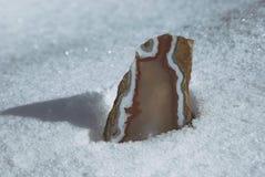 Primer de la piedra de la calcedonia de la ágata contra un fondo del invierno de la nieve Imágenes de archivo libres de regalías