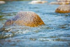 Primer de la piedra con los rápidos del agua en el río Imagen de archivo libre de regalías