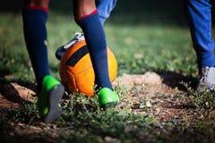 Primer de la pierna del niño pequeño que juega a fútbol en campo de fútbol Fútbol, entrenamiento del fútbol en un campo de fútbol Fotos de archivo libres de regalías