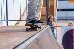Primer de la pierna del patinador en un monopatín Foto de archivo libre de regalías