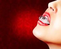 Primer de la pizca roja de los labios un cubo de hielo Imagen de archivo