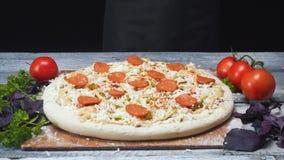 Primer de la pizza cubierto con los pedazos de embutido de cerdo y de queso que mienten en un tablero de madera cerca de los toma almacen de metraje de vídeo