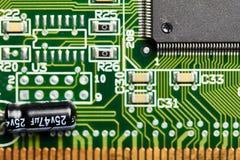 Primer de la placa de circuito impresa con el microchip, el condensador y otros elementos micro integrados Imágenes de archivo libres de regalías