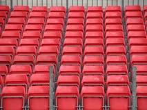 Primer de la plataforma del concierto con filas de asientos plásticos rojos Foto de archivo libre de regalías