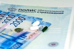 Primer de la política rusa del seguro médico, de los billetes de banco rusos del efectivo y de algunas píldoras Rublos de Rissian imágenes de archivo libres de regalías