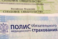Primer de la política rusa del seguro médico y del pasaporte ruso y algunas píldoras en fondo azul imagenes de archivo