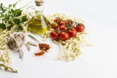 Primer de la receta típica italiana de las pastas: pastas hechas a mano de la harina de trigo de trigo duro, tomates, ajo, aceite foto de archivo