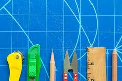 Primer de la regla, tijeras, cortador, lápiz en la estera azul del corte foto de archivo