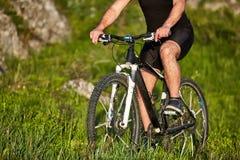 Primer de la rueda de una bicicleta y de las piernas del ciclista en el prado Fotos de archivo