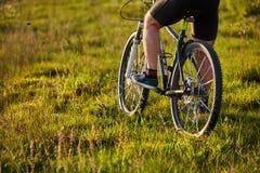 Primer de la rueda de una bicicleta y de las piernas del ciclista en el prado Fotos de archivo libres de regalías