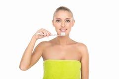 Primer de la señora joven hermosa que celebra el cepillo de dientes y la sonrisa Fotografía de archivo