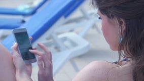 Primer de la señora morena joven que manda un SMS, enviando SMS, usando el teléfono almacen de video