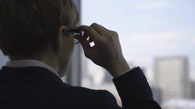 Primer de la situación joven del hombre de negocios cerca de la ventana y de tomar sus vidrios apagado en oficina Visión posterio almacen de video