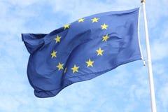 Primer de la sola bandera europea con doce estrellas amarillas que agitan en el viento delante del cielo azul fotos de archivo libres de regalías
