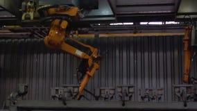 Primer de la soldadura de las piezas de metal por la soldadora en la fábrica escena Robot-soldadores industriales grandes del aut almacen de metraje de vídeo