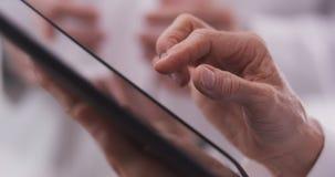 Primer de la tableta conmovedora de la mano de la mujer de mediana edad Foto de archivo libre de regalías