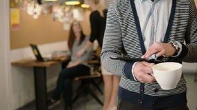 Primer de la tableta de la pantalla táctil de las aplicaciones de hombre joven de las manos y del café de consumición en la ofici metrajes