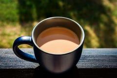 Primer de la taza azul de café de la mañana lista para beber en Ledge Of Balcony imagen de archivo
