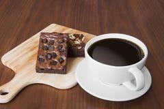 Primer de la taza de café sólo y de brownie en una tabla de madera fotos de archivo