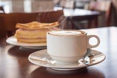Primer de la taza de café con un bocadillo en la cafetería Imagen de archivo libre de regalías