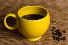 Primer de la taza de café - taza amarilla con las habas Imagenes de archivo