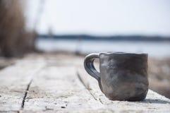 Primer de la taza hecha a mano única con la muestra popular con el lago borroso en fondo fotografía de archivo