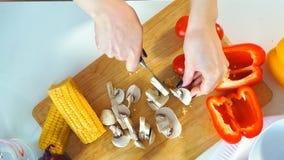 Primer de la visión superior de una mujer joven que corta verduras en la cocina metrajes