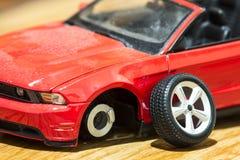 Primer de la vista posterior del coche rojo del juguete después del accidente de carretera Foto de archivo libre de regalías